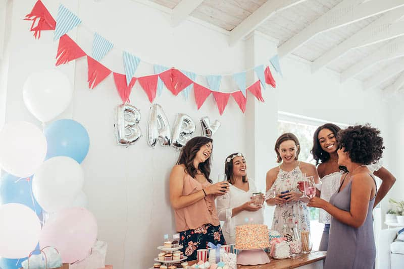 Pregnant woman celebrating baby shower with female friends at home