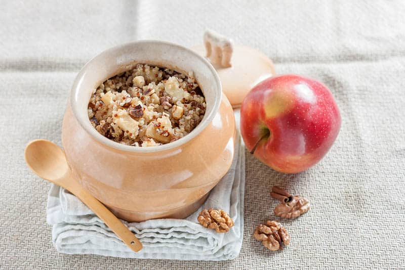 Quinoa porridge with apples, walnuts, cinnamon and cheese in a pot on the cloth