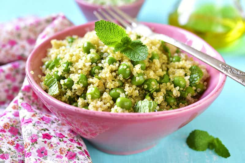 Quinoa salad with green pea and mint in the pink bowl with colorful cloth