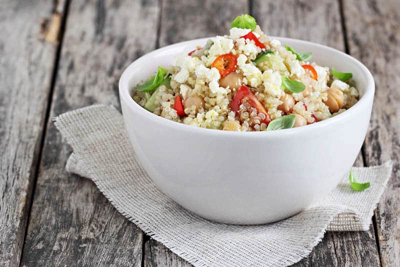 Quinoa salad with vegetables mix, chickpea and cheese on the wooden old table