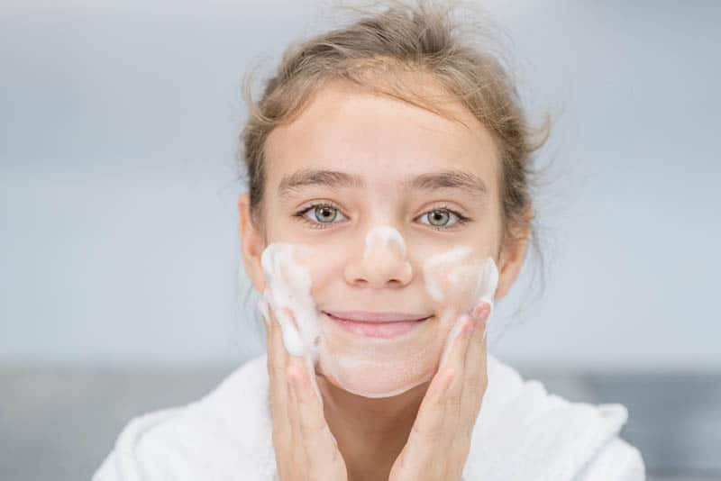 Smiling young girl washes her face in bathroom at home