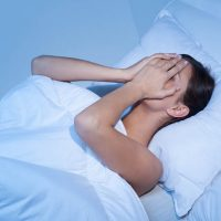young woman in bed covering her face after a nightmare