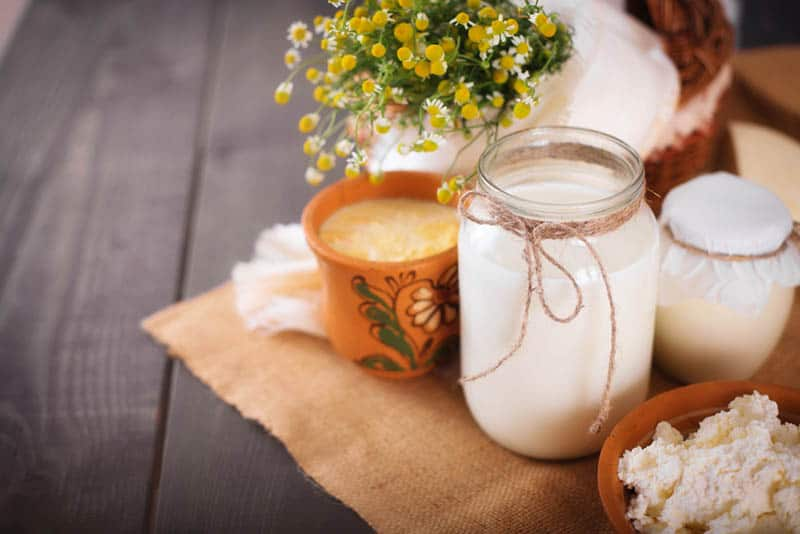 a jar of goat's milk with cheese and yogurt on the table with flowers