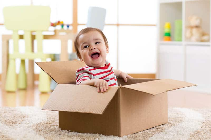 adorable baby boy smiling while sitting in a card box