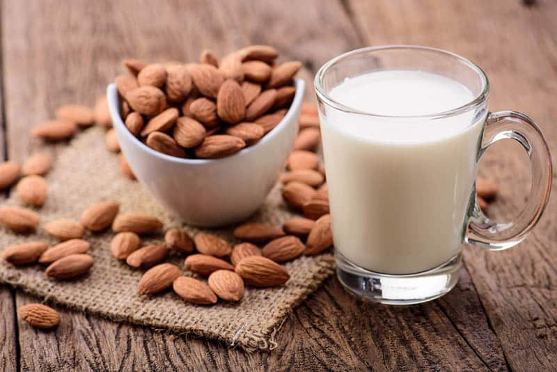 almond milk in glass with almonds on the wooden table