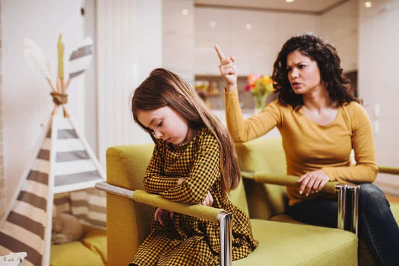 angry mother yelling at her daughter at home
