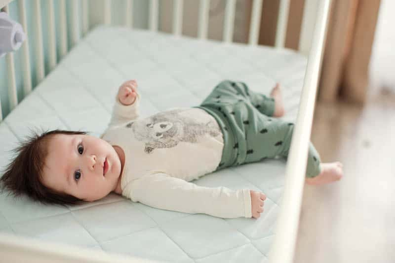 baby boy lying in crib with one leg hanging through the rails