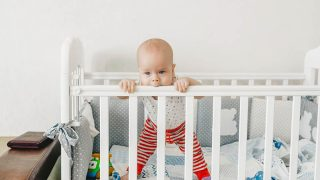 cute baby girl standing in the crib and chewing on the rail