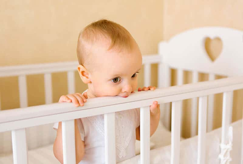 baby girl standing in the crib and chewing rail