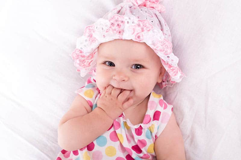 baby girl wearing pink hat chewing her hand on the bed