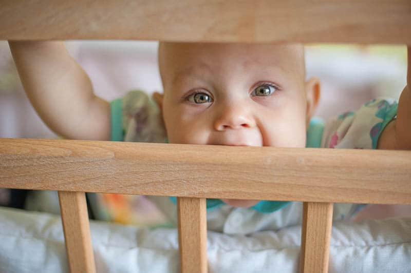baby girl with wonderful eye color chewing crib rails