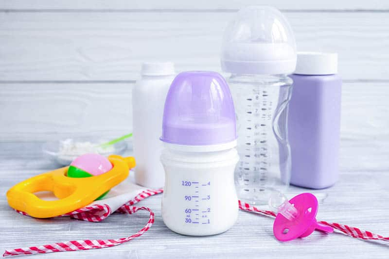 baby milk bottle with pacifier and baby items on the table