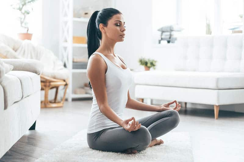 beautiful woman meditates on the floor at home