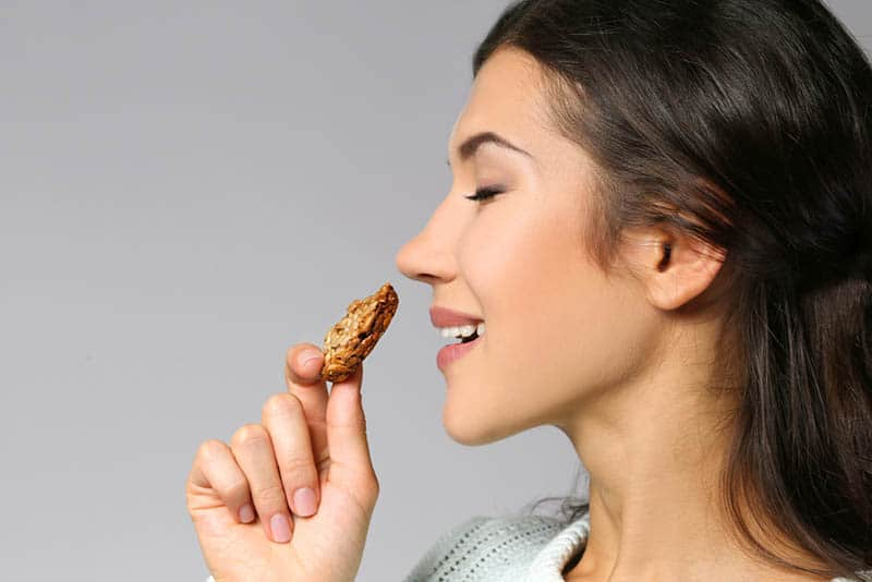 beautiful young woman holding a cookie to eat with closed eyes