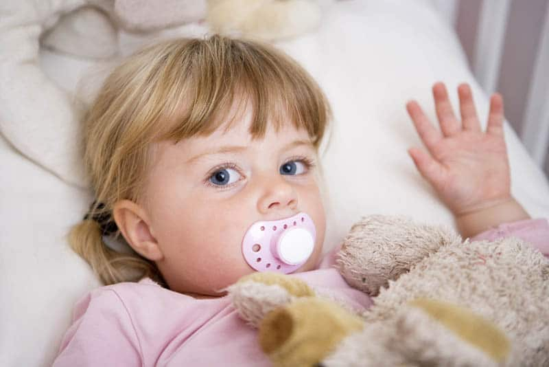 blond little girl with pacifier lying in bed with toy covered with blanket