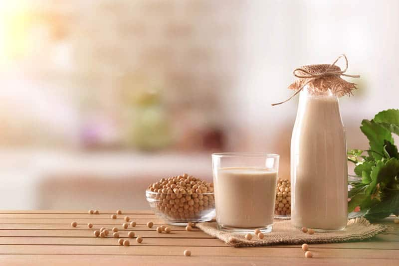 bottle and glass of soy milk with grains on the wooden table