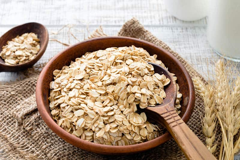 bowl full of oats with wooden spoon on the table