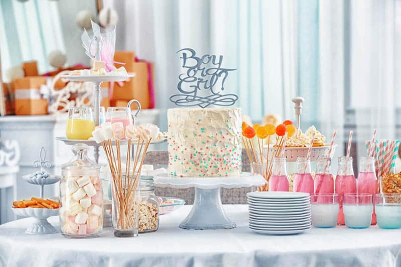 cake and different treats for baby shower party on table
