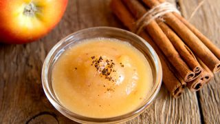 fresh applesauce with apple and cinnamon on wooden table