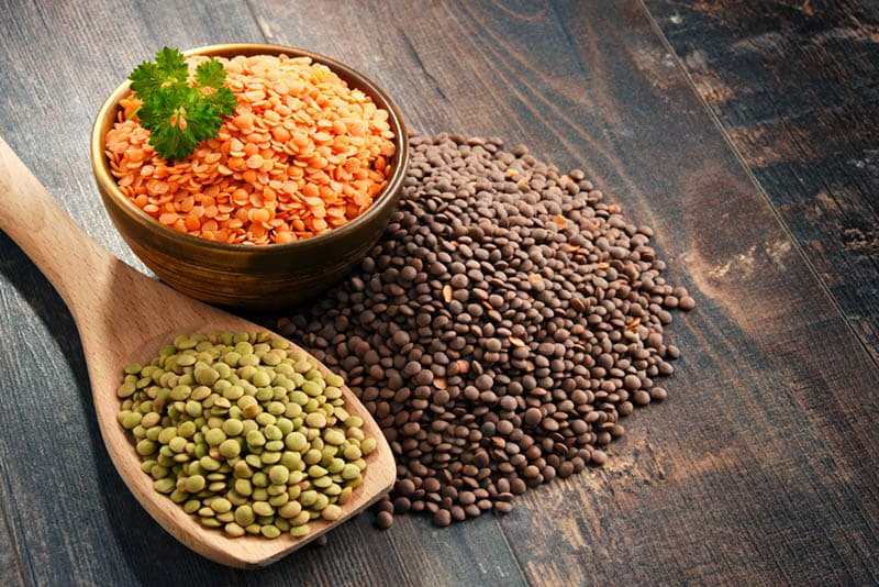 colorful lentils in a bowl and spoon on the wooden table