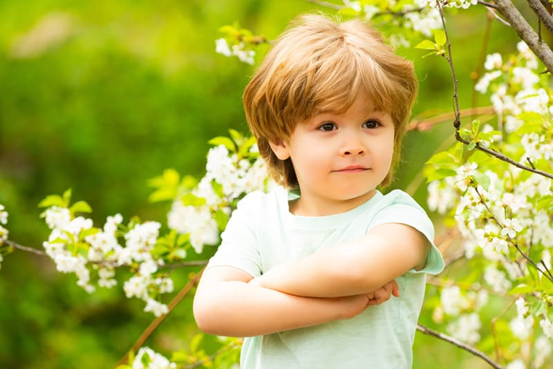 confident little boy posing in the garden with blossom trees