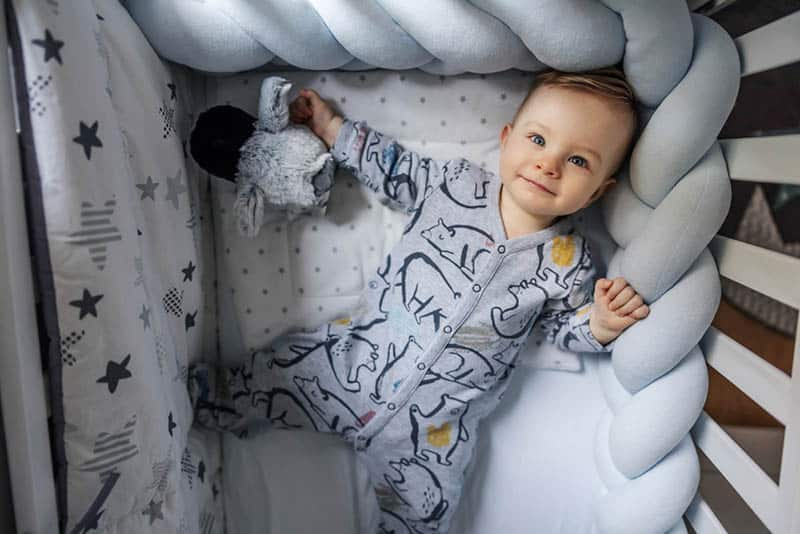 cute baby boy in pijama lying in crib on his back