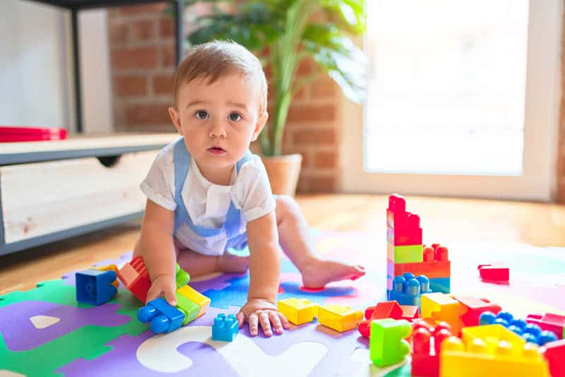 cute baby boy playing on the floor with toys