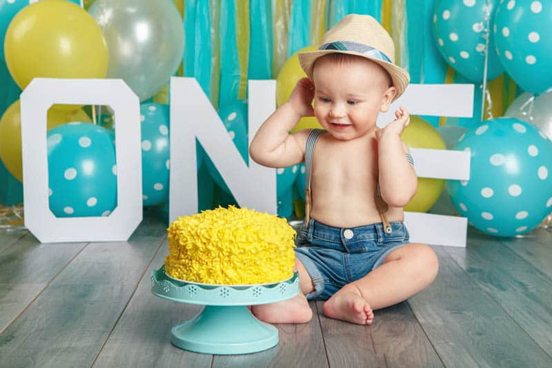 cute baby boy sitting on the floor and smiling to his yellow birthday cake