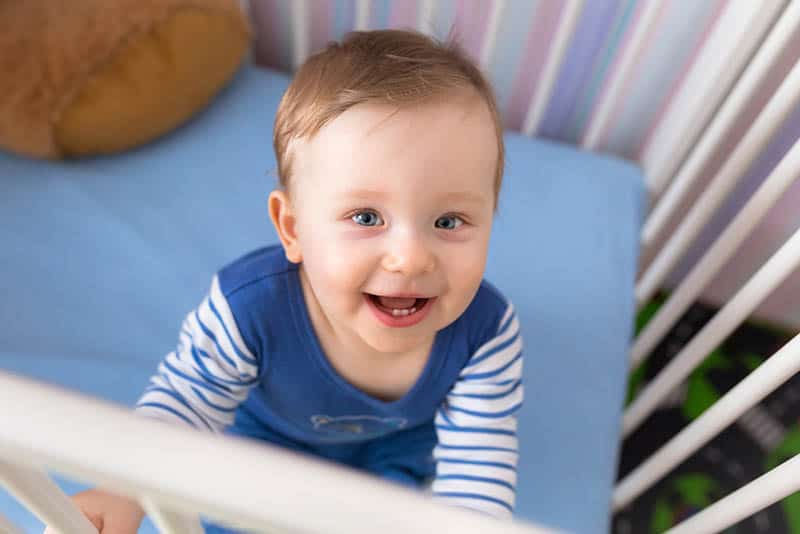 cute baby boy smiling in the crib