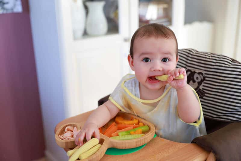 cute baby girl eating vegetables in high chair