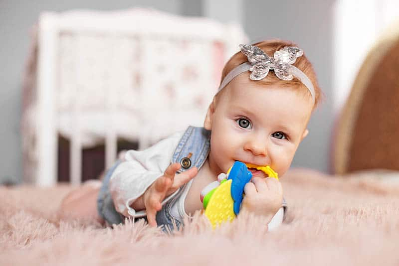 cute baby girl lying on the floor and chewing a teething toy