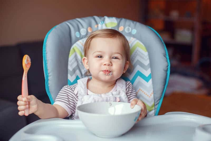 cute baby girl sitting in a high chair with bowl food in front and spoon in hand