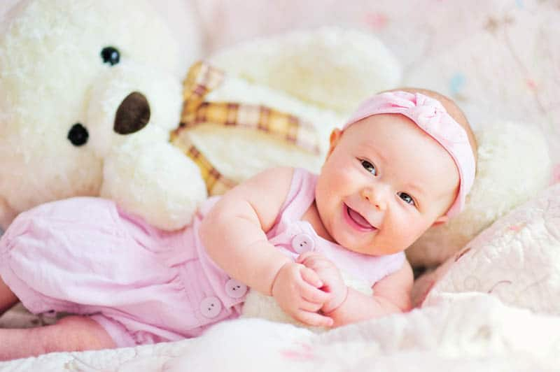 cute baby girl smiling on the bed with teddy bear toy