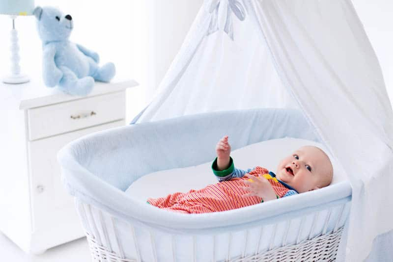 cute baby in colorful pijama lying in the white bassinet in the baby room