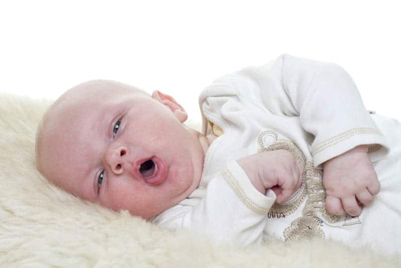 cute baby lying on a sheepskin and coughing