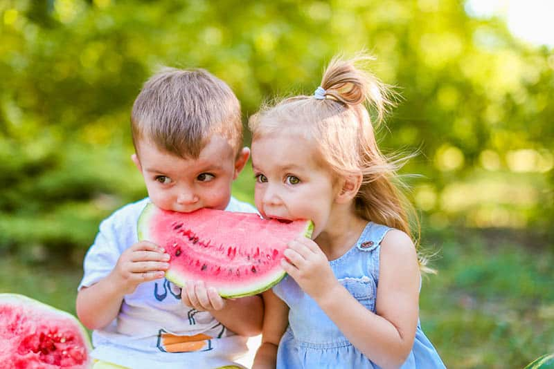cute little boy and a girl eating together watermelon outdoor