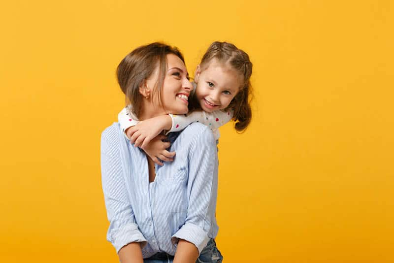 cute little girl hugging her smiling mother