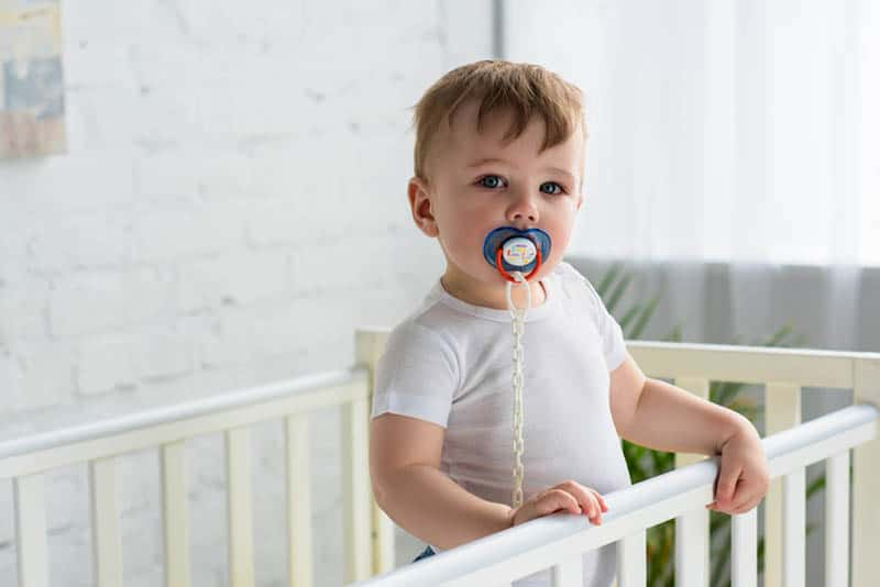 cute toddler standing in the crib holding for rails and sucking pacifier