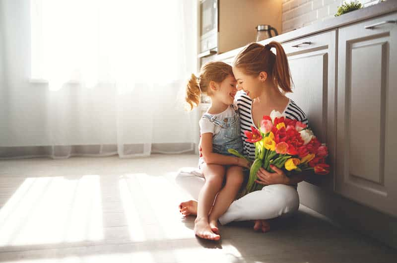 daughter congratulates mother and gives a bouquet of flowers on the floor
