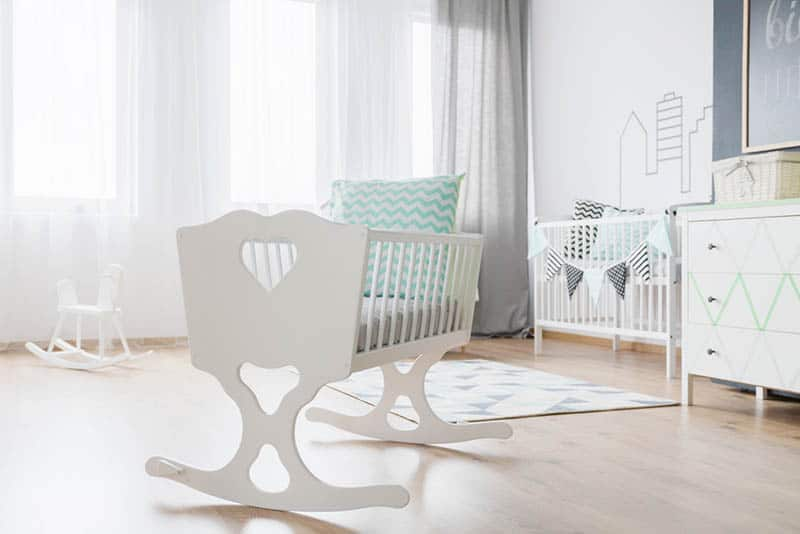 decorative white baby cradle with pillow in the baby room