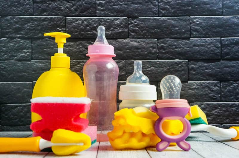 detergent for baby bottles with baby dishes and a sponge on the table