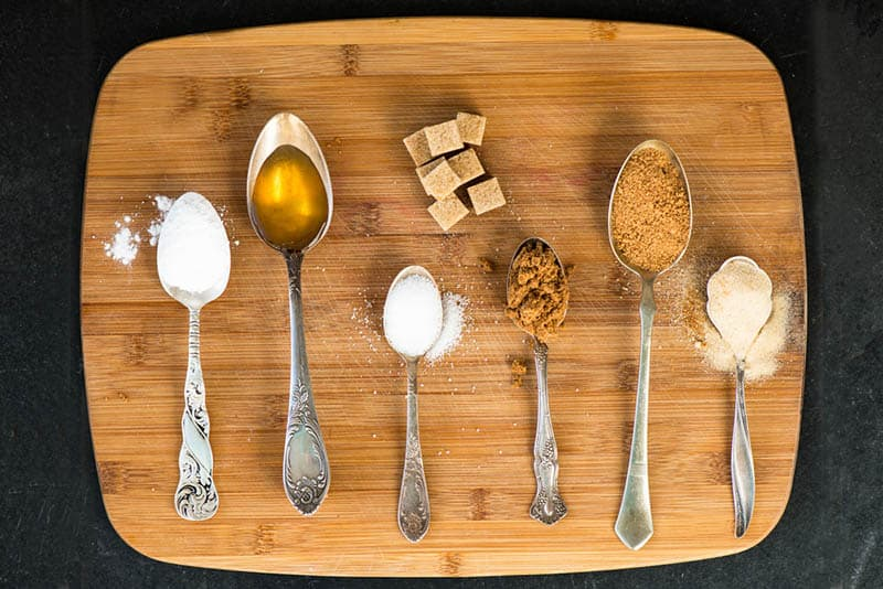 different kinds of sugar in spoons on the wooden cutting board