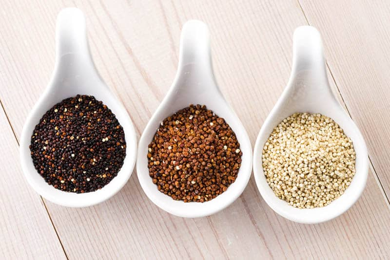 different types of quinoa grain in three white spoon bowles on the wooden table