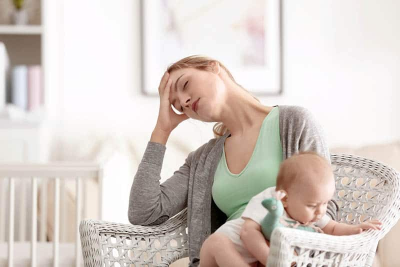 exhausted mother holding baby in a chair at home