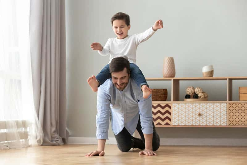 father carrying son on back and playing while crawling on the floor