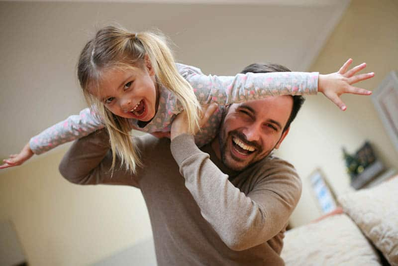 father holding his daughter in the air playing piggy ride