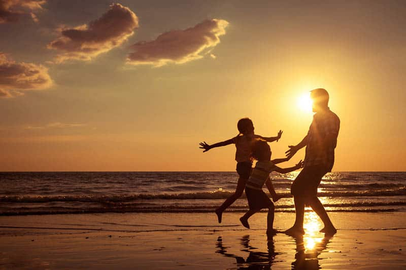 father playing with his kids on the beach at sunset