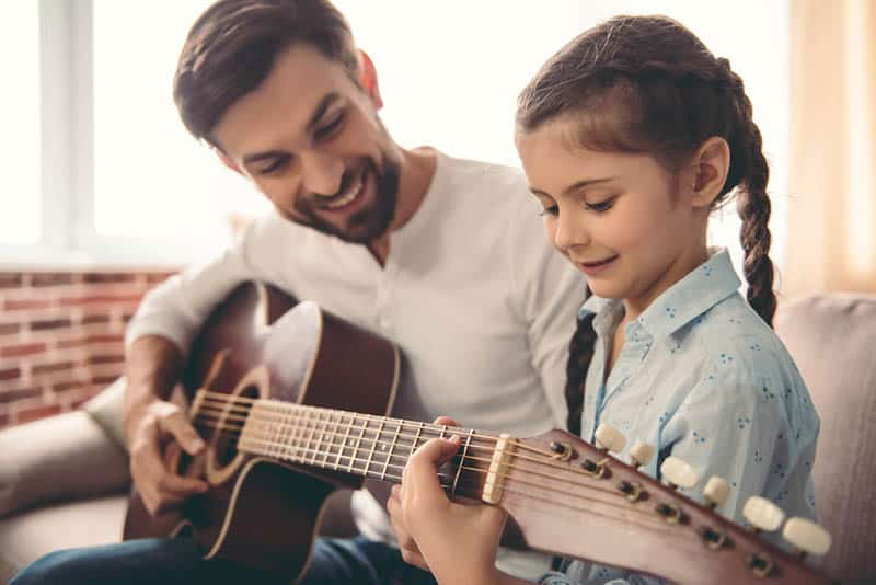 father teaching daughter to play a guitar at home on the couch