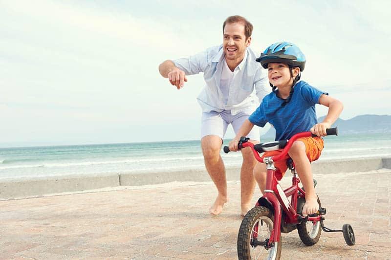 father teaching son to ride a bike near the beach
