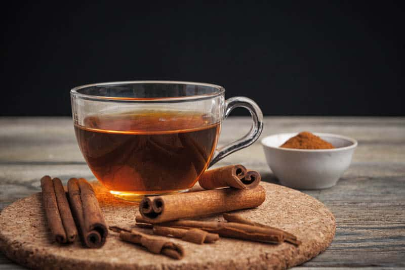 glass of cinnamon tea with cinnamon sticks on the board